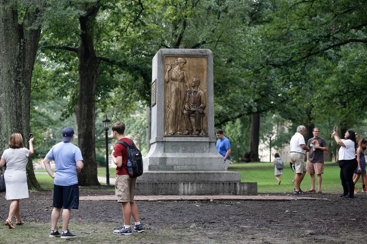 People gather around the remainder of the Silent Sam monument after it was toppled from its pedestal by protesters at the Uni