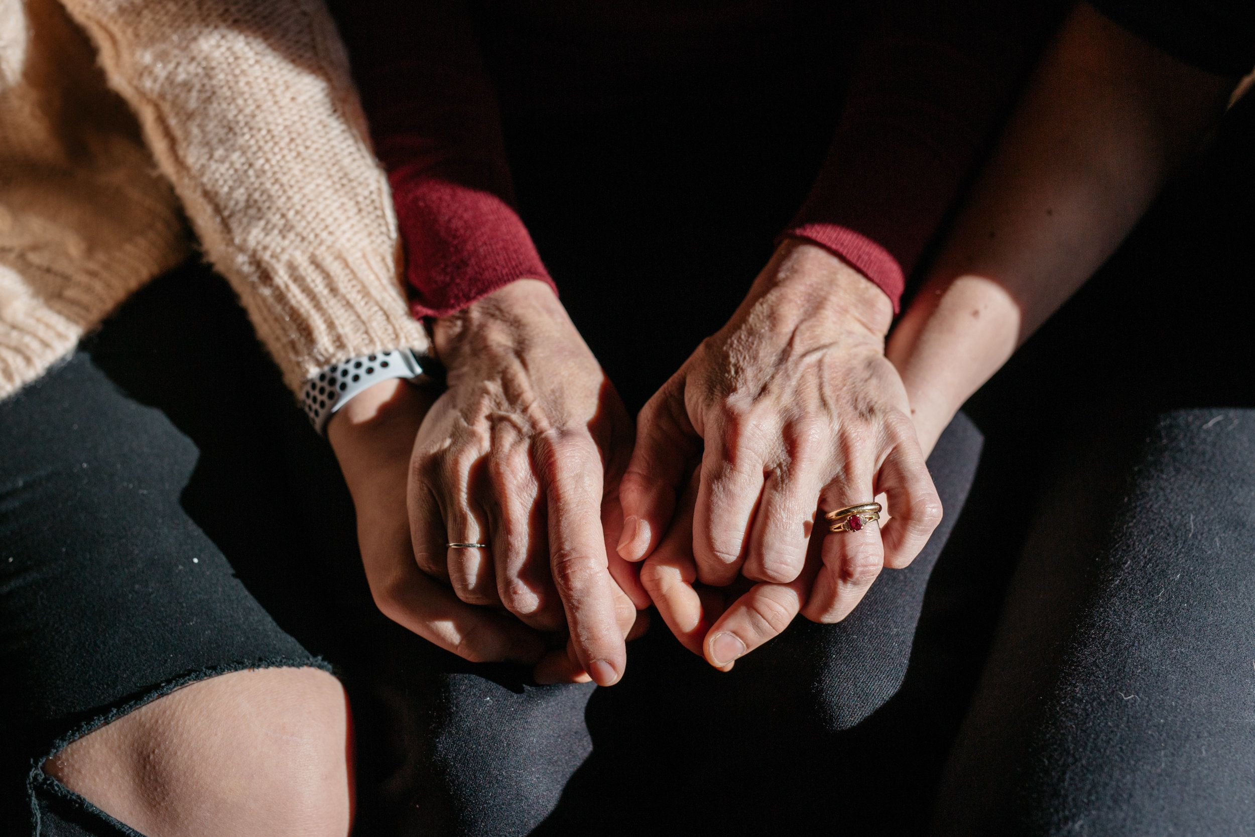 Suzanne Thomashow, center, holds the hands of her daughters Amanda, right, and Jessica, left.