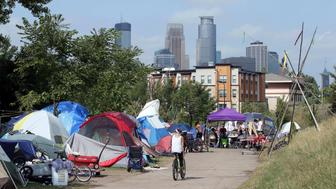 In this Sept. 14, 2018 photo, the Minneapolis skyline rises behind a homeless encampment that continues growing in south Minneapolis. The Minneapolis City Council voted Wednesday, Sept. 26 to approve a temporary site to house hundreds of homeless people who have been living in tents at the encampment just south of downtown. (AP Photo/Jim Mone)