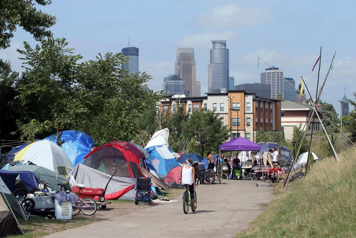In this Sept. 14, 2018 photo, the skyline rises behind a homeless encampment in south Minneapolis.