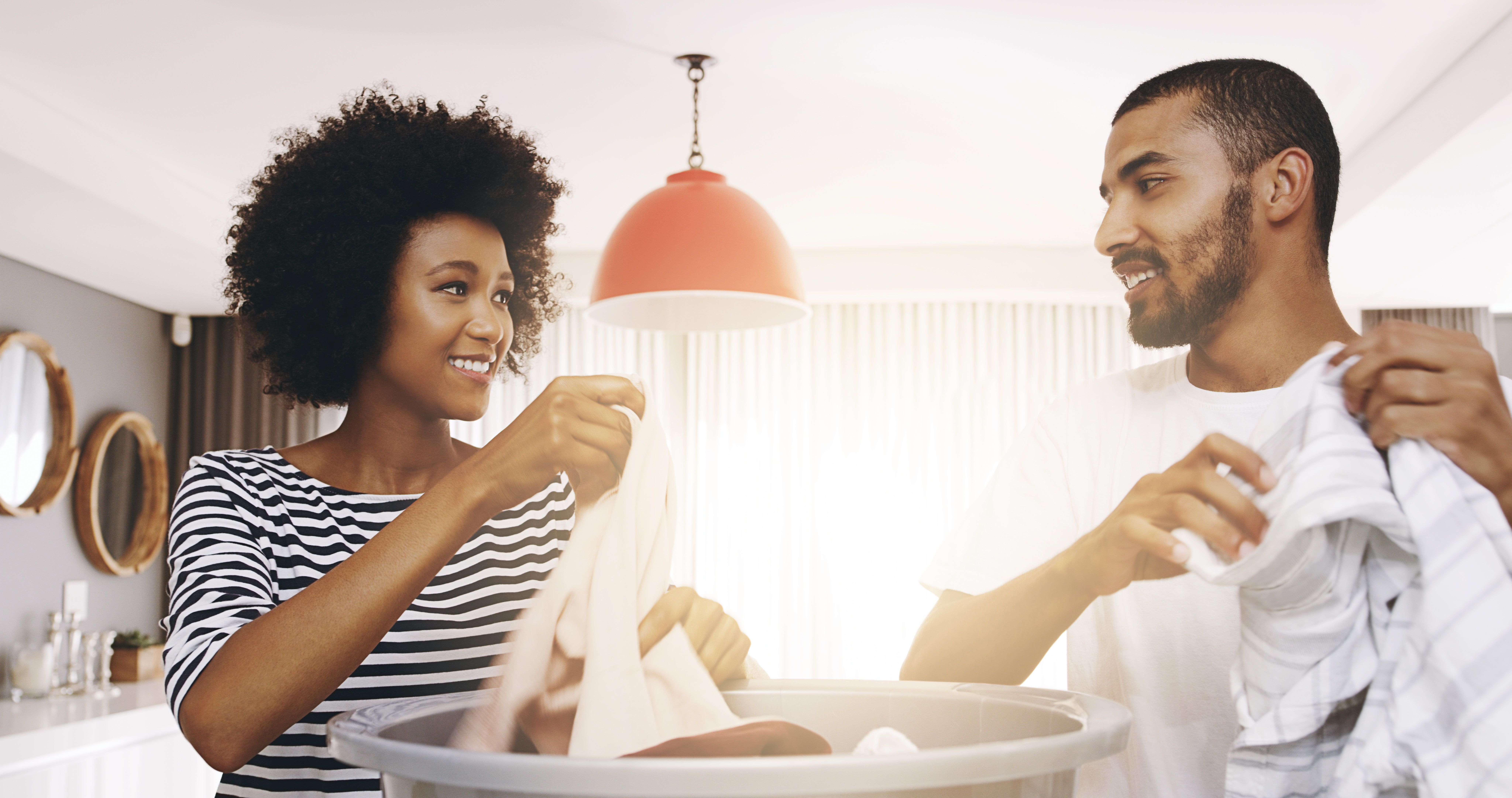 Shot of a cheerful young couple working together and sorting out washing at home during the day
