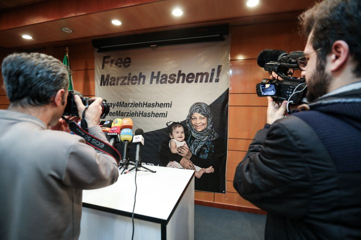 Journalists photograph and film a poster depicting Marzieh Hashemi, during a press conference by her employer Press TV in Teh