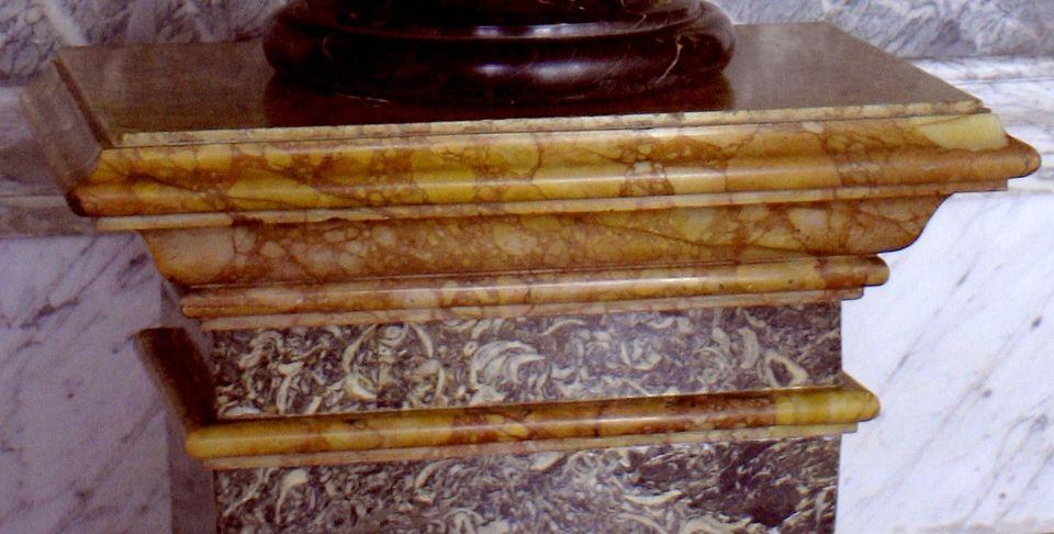 Gros plan sur la partie supérieure d'une gaine, dont la corniche et la cimaise sont en marbre...