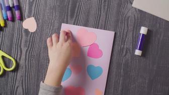 Top view. Close up girl's hands glueing a card. Valentine's Day.