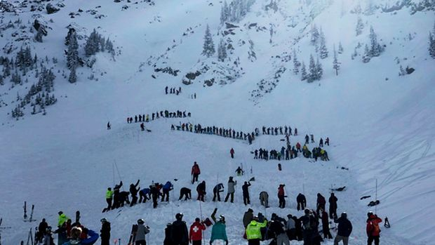 People search for victims after an avalanche buried multiple people near the highest peak of Taos Ski Valley, one of the biggest resorts in New Mexico, Thursday, Jan. 17, 2019. The avalanche rushed down the mountainside of the New Mexico ski resort on Thursday, injuring at least a few people who were pulled from the snow after a roughly 20-minute rescue effort, a resort spokesman said. (Morgan Timms/Taos News via AP)