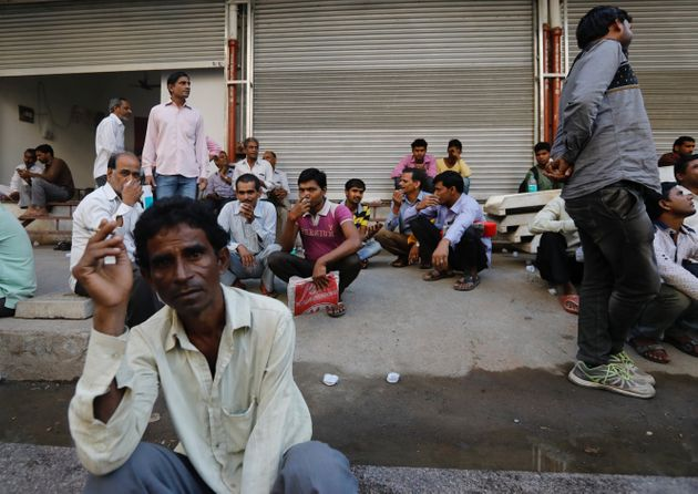 Unorganised sector workers sit on a footpath as they wait to get hired for work in Mumbai on November...