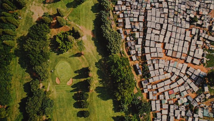 A sprawling informal settlement sits near the manicured fairways of a golf course in Durban, South Africa. The wealth of bill