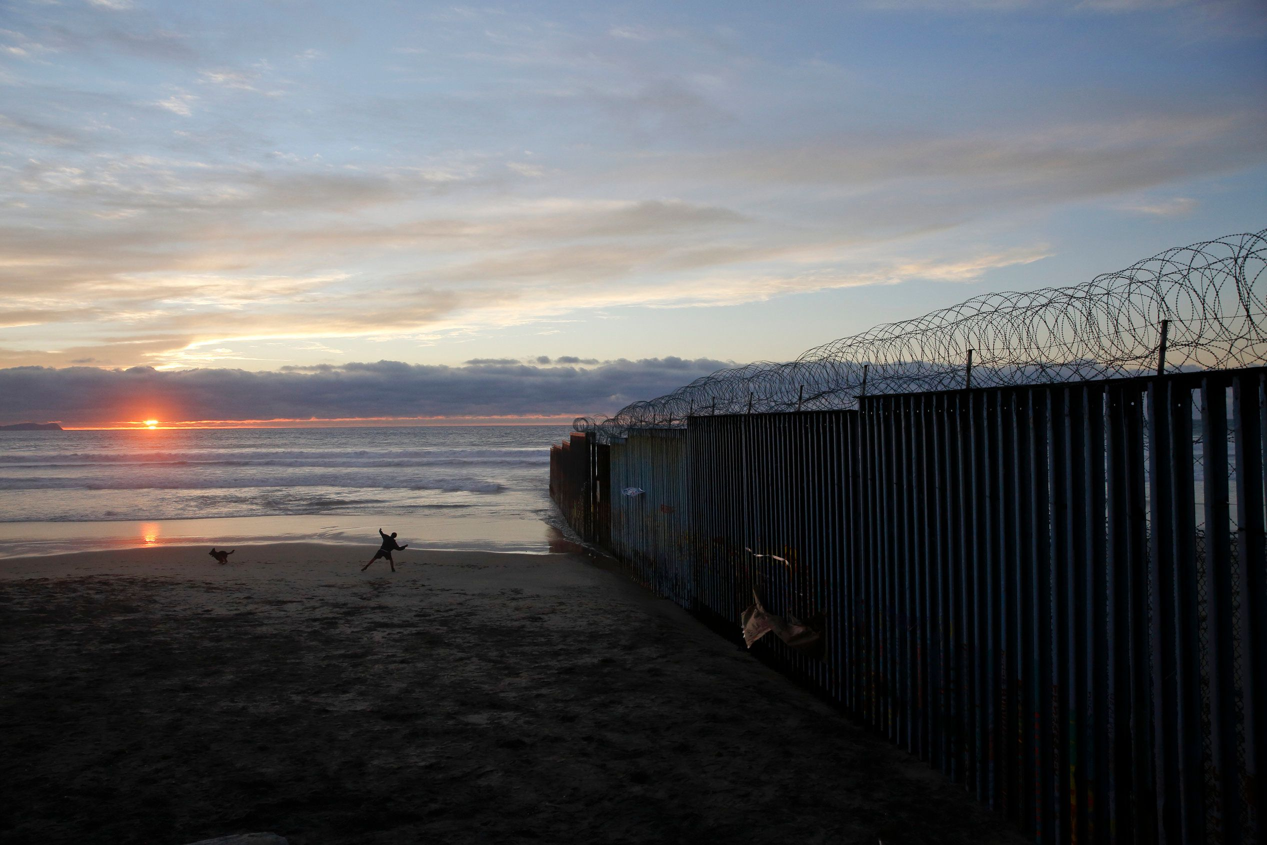 """FILE - In this Jan. 9, 2019, file photo, a man throws a ball for his dog next to the border wall topped with razor wire in Tijuana, Mexico. In his demands that Congress set aside $5.7 billion for a border wall, President Donald Trump insists a physical barrier would stop heroin entering the U.S. from Mexico. But U.S. statistics, analysts and testimony at the trial of drug kingpin Joaquin """"El Chapo"""" Guzman in New York show that most hard drugs entering the U.S. from Mexico come through land ports of entry staffed by agents, not open sections of the border. (AP Photo/Gregory Bull, File)"""