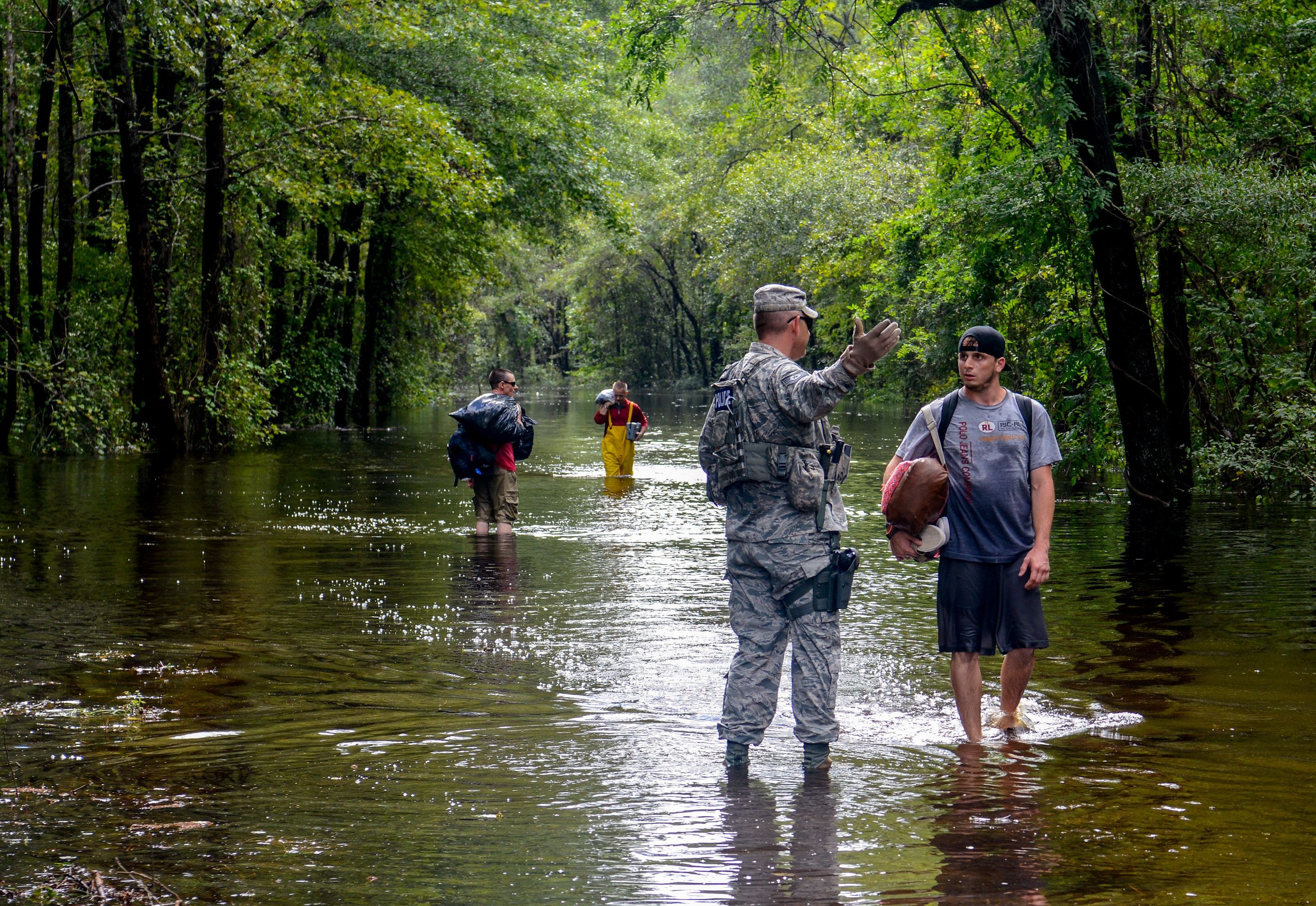A U.S. Air Force member assigned to the South Carolina Air National Guard assists citizens during evacuation efforts after Hurricane Florence hit in September 2018.