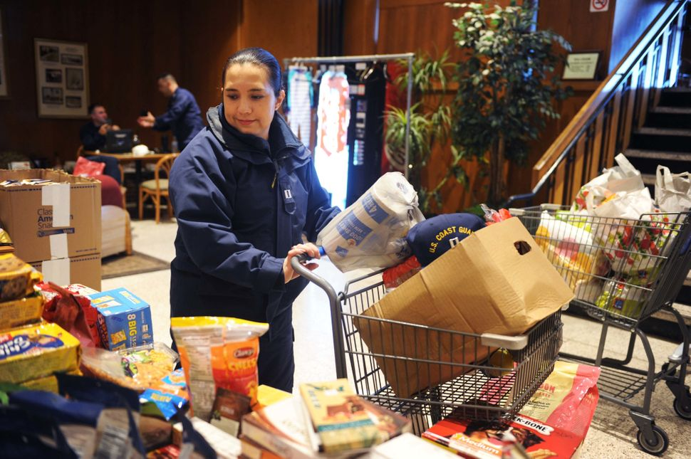 Jackie Ramirez, a Coast Guard Academy instructor, picks up donated items at a pop-up food pantry for Coast Guard members who