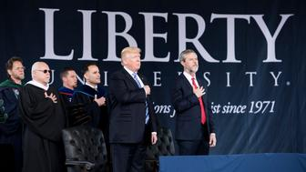 US President Donald Trump (2nd R), President of Liberty University Jerry Falwell (R), and others participate in the Pledge of Allegiance during Liberty University's commencement ceremony May 13, 2017 in Lynchburg, Virginia. / AFP PHOTO / Brendan Smialowski        (Photo credit should read BRENDAN SMIALOWSKI/AFP/Getty Images)