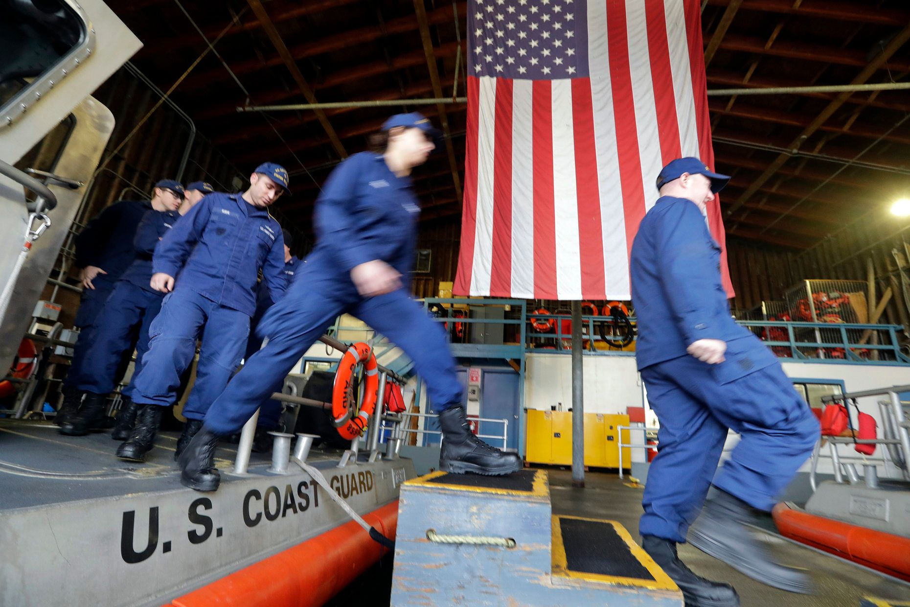 Coast Guardsmen and -women, who missed their first paycheck a day earlier because of the government shutdown, walk off a 45-f