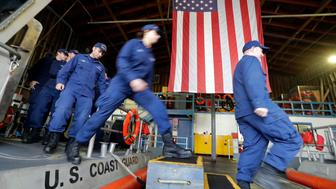 FILE In this Wednesday, Jan 16, 2019, file photo, U.S. Coast Guardsmen and women, who missed their first paycheck a day earlier during the partial government shutdown, walk off a 45-foot response boat during their shift at Sector Puget Sound base in Seattle. San Antonio-based USAA, a military personnel insurer and financial services company, said Wednesday they has donated $15 million for interest-free loans to Coast Guard members during the partial U.S. government shutdown. The funds will be disbursed by Coast Guard Mutual Assistance. The American Red Cross Hero Care Center will assist. (AP Photo/Elaine Thompson, File)