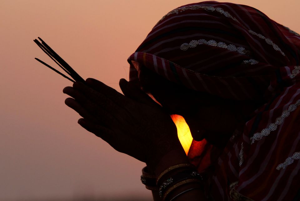 A woman devotee offers prayers to the setting sun on the 20th anniversary of the Babri mosque demolition...
