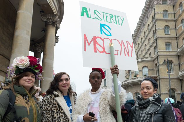 Demonstrators at a women's march in London, holding a sign reading,