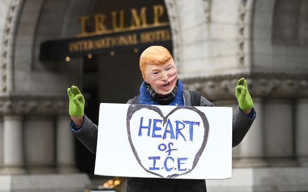 A man in a Donald Trump face mask poses in front of the Trump International Hotel during the march in...