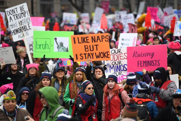 Participants in the Women's March in Washington, D.C., holding numerous signs, one of which reads,