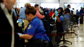 Transportation Security Administration (TSA) agents screen passengers at a security checkpoint at Hartsfield-Jackson Atlanta International Airport amid the partial federal government shutdown, in Atlanta, Georgia, U.S., January 18, 2019. Picture taken through a window.  REUTERS/Elijah Nouvelage
