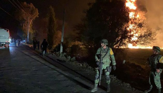 Military personnel watch as flames engulf an area after a ruptured fuel pipeline exploded in