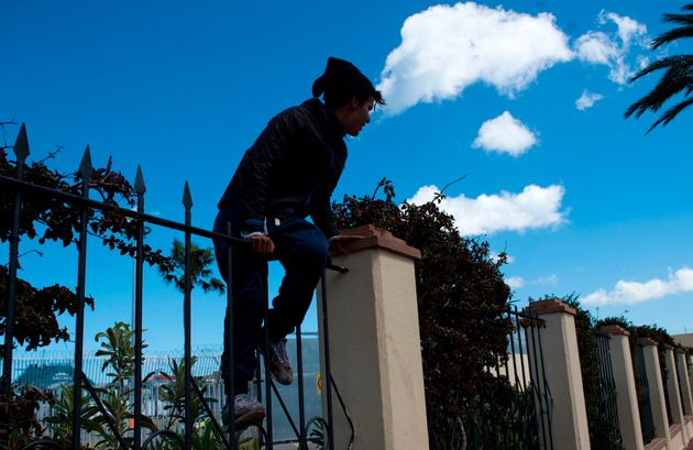 Un jeune marocain escalade une clôture dans le port de Sebta, en avril