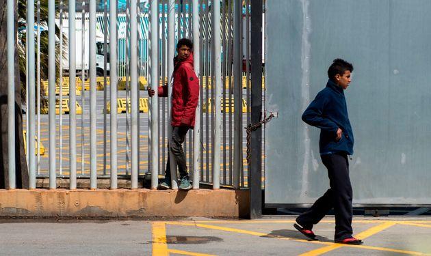 De jeunes marocains marchant près d'une clôture dans le port de Sebta, en avril 2018, espèrent...