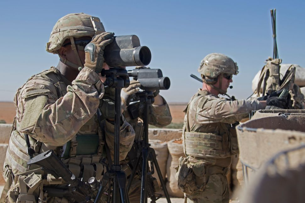 In this Nov. 1, 2018, photo released by the U.S. Army, soldiers surveil the area during a combined joint patrol in Manbij, Sy