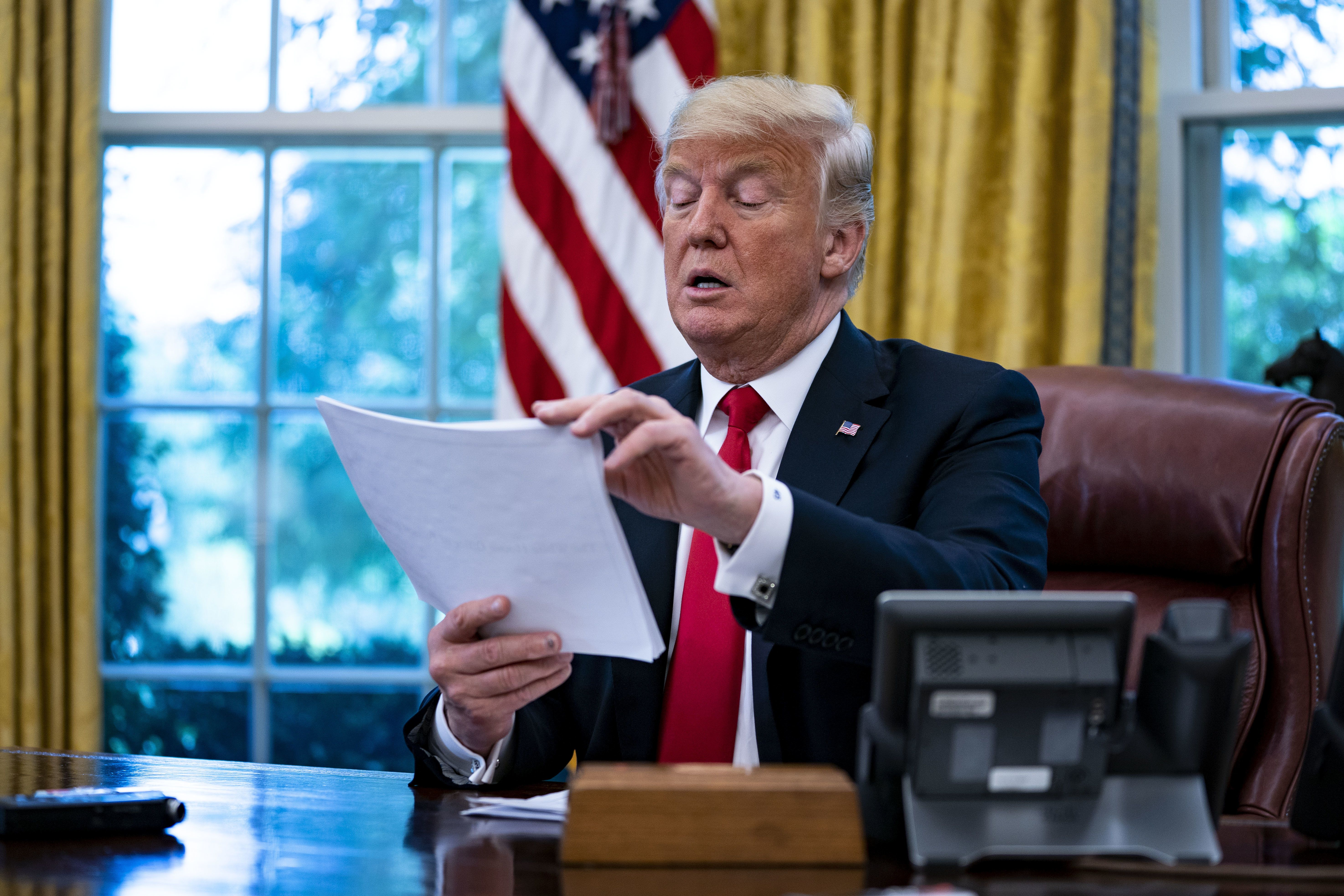 U.S. President Donald Trump reviews papers during an interview in the Oval Office of the White House in Washington, D.C., U.S., on Thursday, Aug. 30, 2018. Trumpsaid he doesn't regret appointing Jerome Powell as Federal Reserve chairman, even after criticizing interest rate increases by the central bank. Photographer: Al Drago/Bloomberg via Getty Images