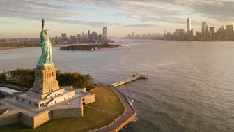 statue of liberty with nyc next to it