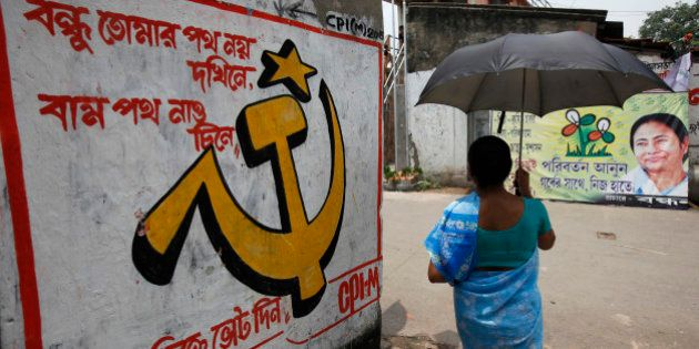 A woman carrying an umbrella walks past political murals and posters in Kalighat district, the neighbourhood...