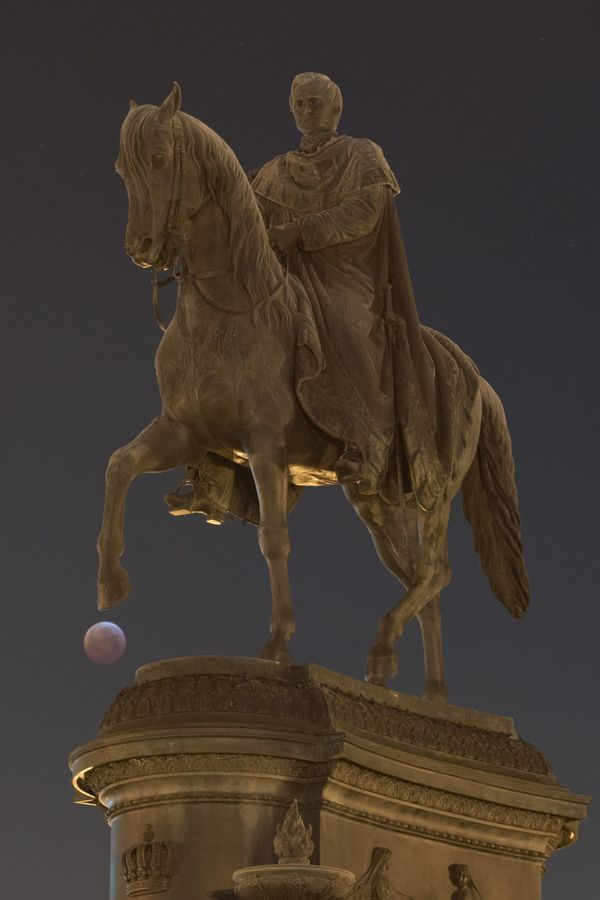 The super blood moon behind the equestrian statue of the Saxon king Johann in Dresden, Germany, Jan. 21.