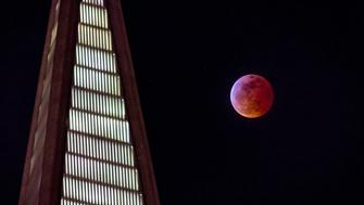 A super blood wolf moon rises behind the TransAmerica building in San Francisco, California, U.S., on Sunday, Jan. 20, 2019. Our first full moon of the year is also a special kind of total lunar eclipse thats been dubbed a 'super blood wolf moon.' This total lunar eclipse or 'blood moon' is simultaneously a 'supermoon' because of the Moon's close proximity to Earth and it happens to coincide with the 'wolf moon', the traditional name for the January full moon. Photographer: David Paul Morris/Bloomberg via Getty Images