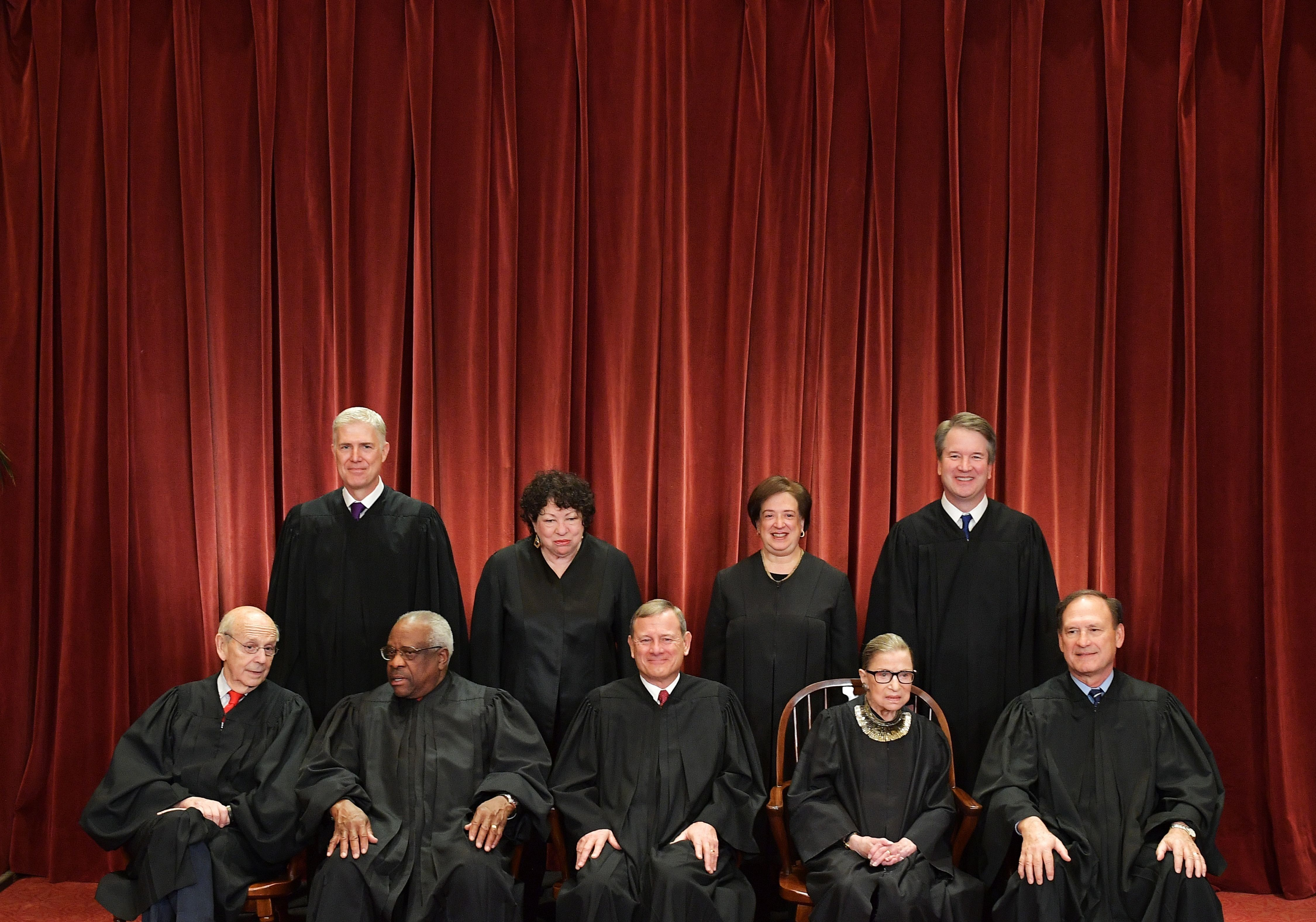 Justices of the US Supreme Court pose for their official photo at the Supreme Court in Washington, DC on November 30, 2018. - Seated from left: Associate Justices Stephen Breyer, Clarence Thomas, Chief Justice John  Roberts, Ruth Bader Ginsburg and Samuel Alito. Standing from left: Associate Justices Neil Gorsuch, Sonia Sotomayor, Elena Kagan and Brett Kavanaugh (Photo by MANDEL NGAN / AFP)        (Photo credit should read MANDEL NGAN/AFP/Getty Images)