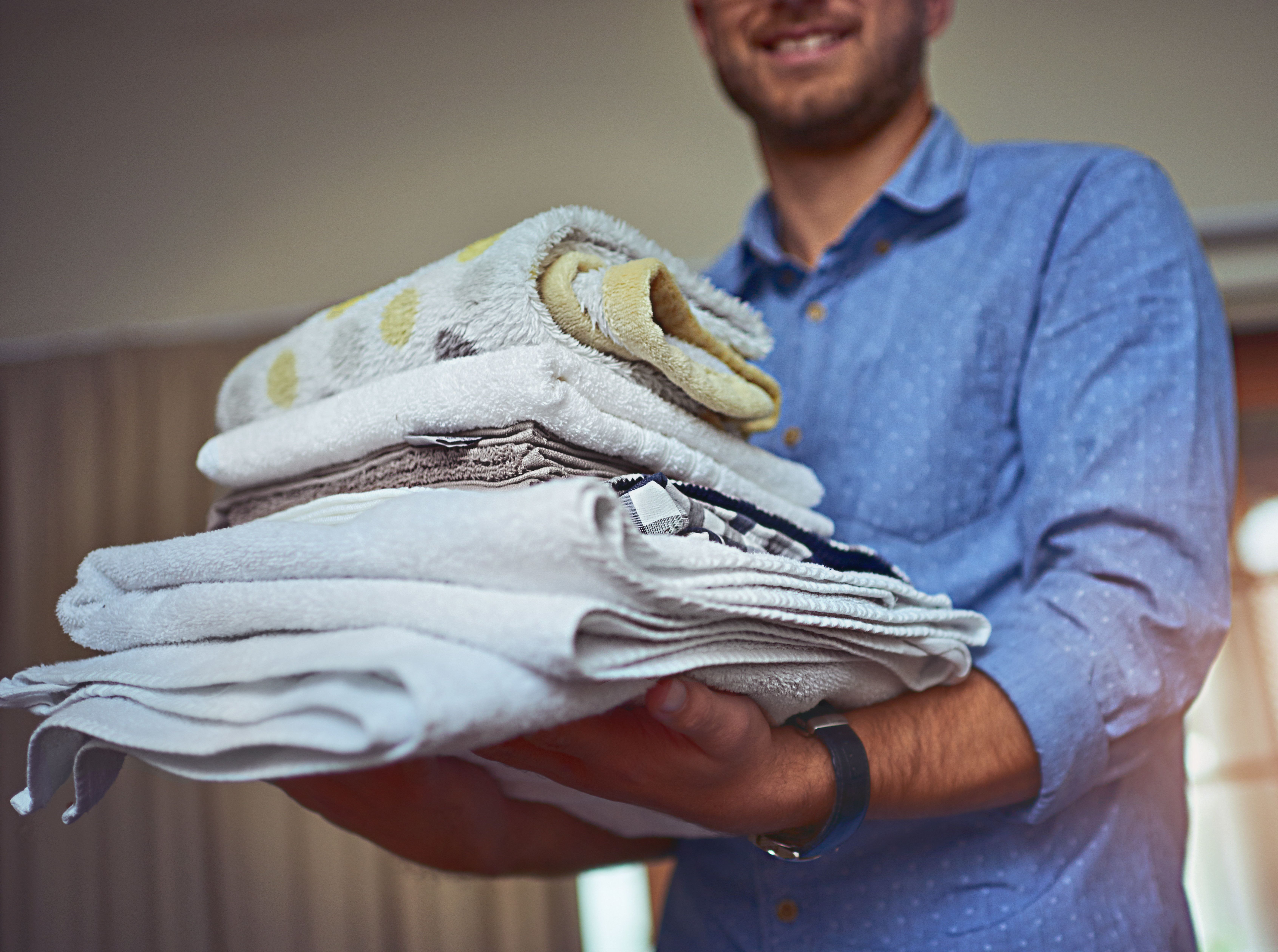 Cropped shot of a young man holding a load of freshly folded clean laundry