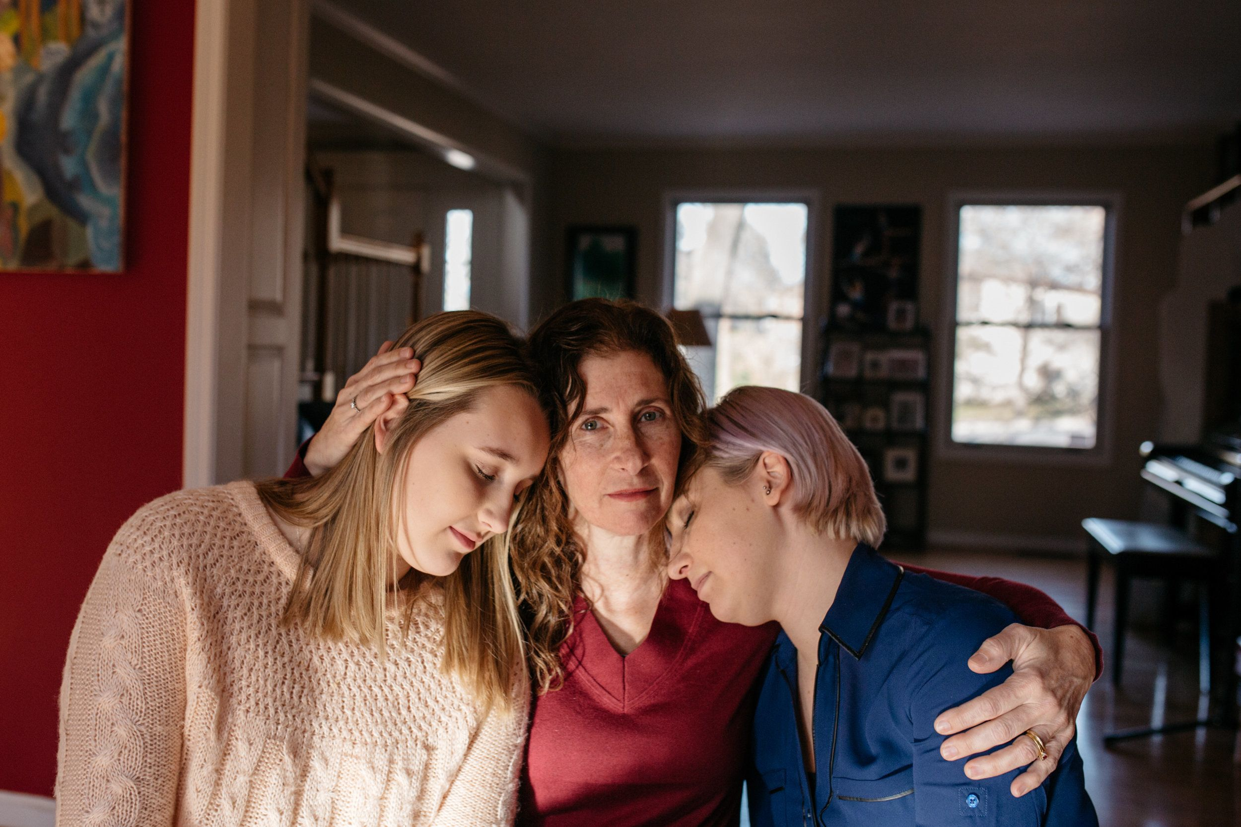 Suzanne Thomashow (center), a pediatrician and mother to Amanda (right) and Jessica (left), Nassar survivors inside their home in Lansing, Michigan.