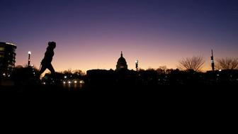 A woman walks by the U.S. Capitol is on day 32 of a partial government shutdown as becomes the longest in U.S. history in Washington, U.S., January 22, 2019. REUTERS/Carlos Barria