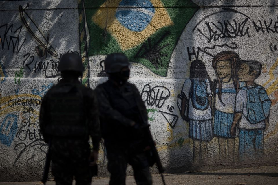Soldiers patrol a favela neighborhood in Rio de Janeiro in August 2018, a day after at least 11...