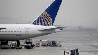 A luggage cart rolls near a United Airlines jet at Newark Liberty International Airport, Tuesday, Jan. 8, 2019, in Newark, N.J. Transportation Security Administration agents among other airport employees have been working without pay during the partial government shutdown. (AP Photo/Julio Cortez)