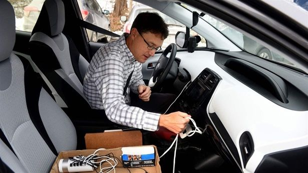 Corey Chase, a telecommunications analyst with Vermont's Department of Public Service, checks his power cord in Royalto
