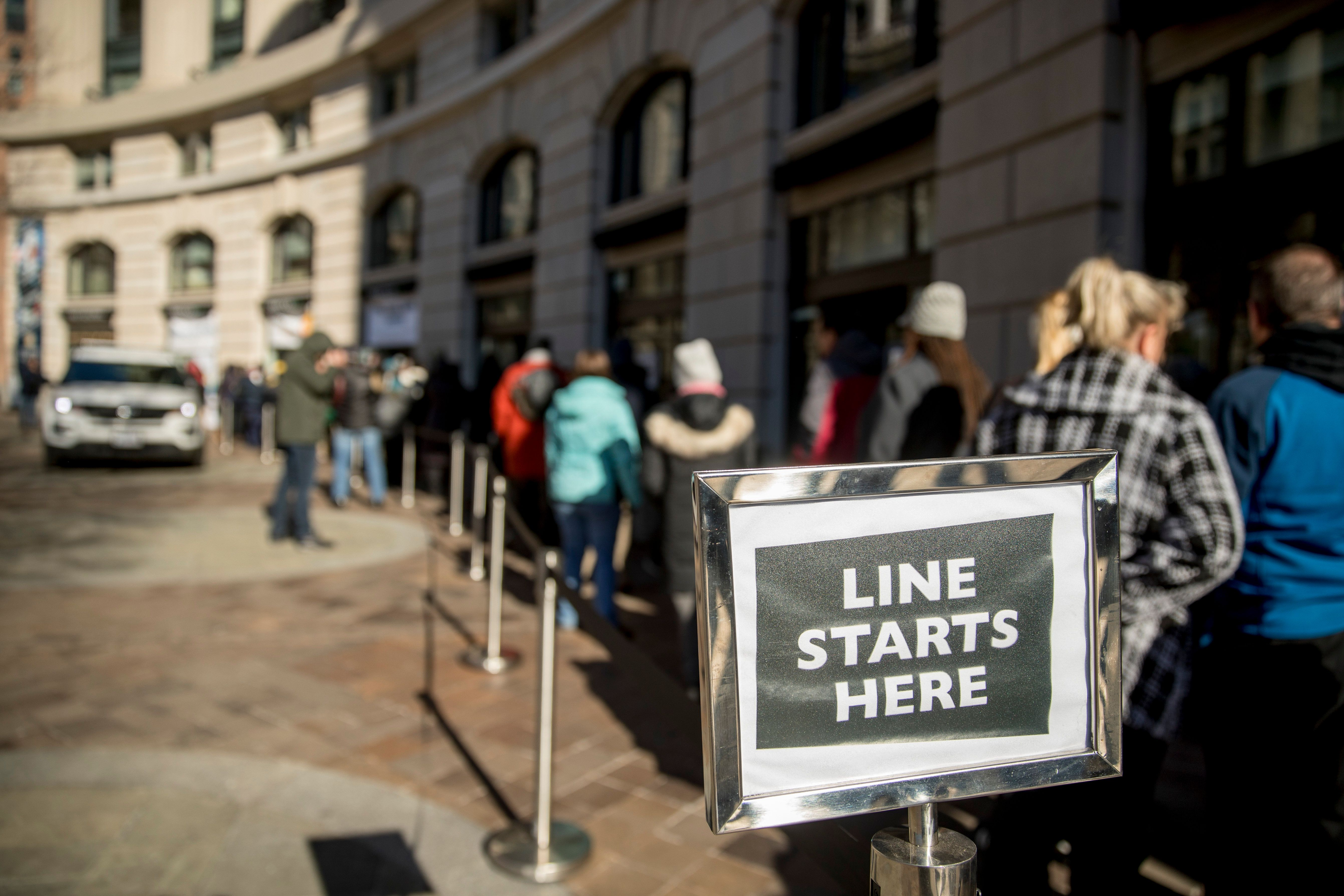 Furloughed workers wait in line on Tuesday to receive food and supplies from World Central Kitchen, the not-for-profit organi