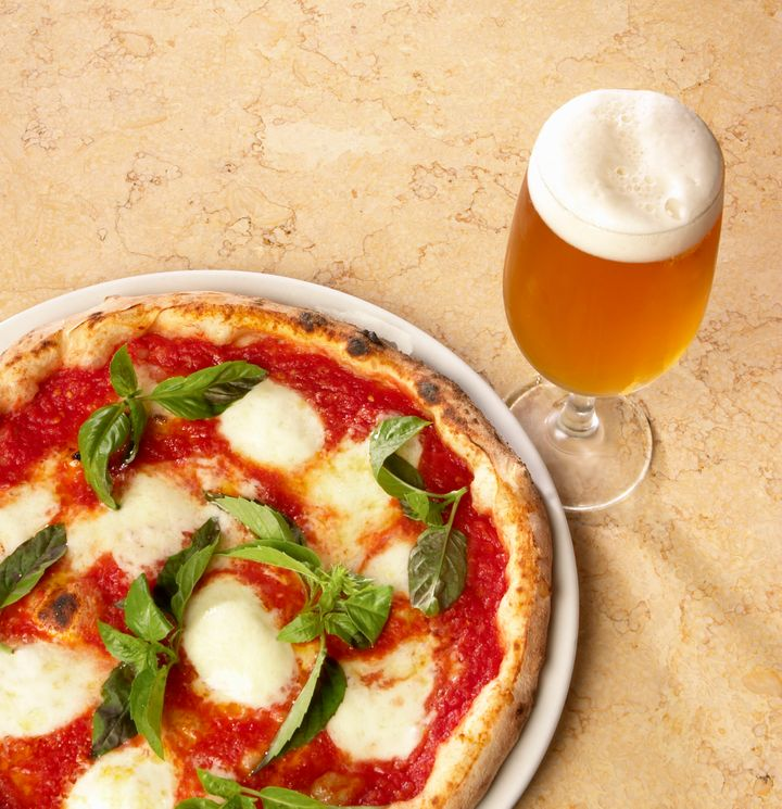 A autêntica pizza napolitana vem acompanhada de cerveja.