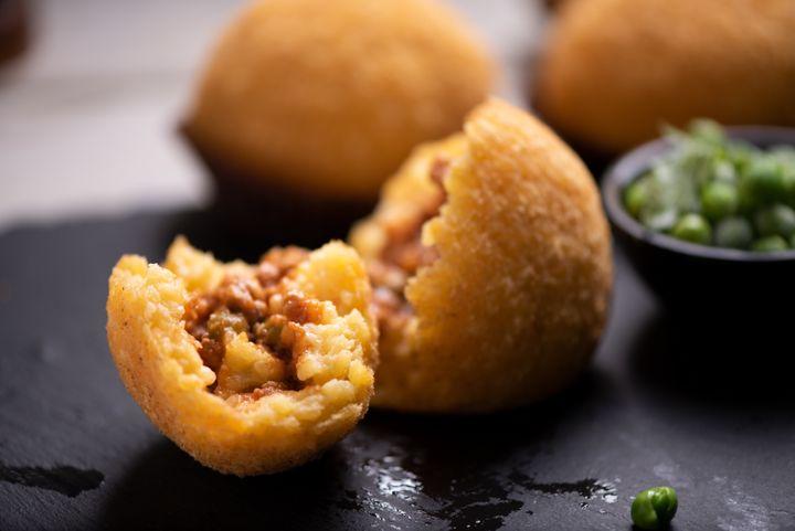 Arancini é um salgado italiano recheado de risoto.