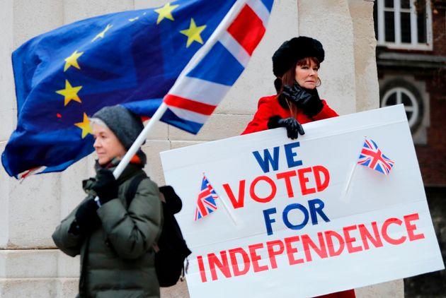 EU 깃발과 영국 깃발을 든 한 시민이 브렉시트 찬성 피켓 시위를 벌이는 한 시민(오른쪽) 앞을 지나쳐가고 있다. 런던, 영국. 2019년