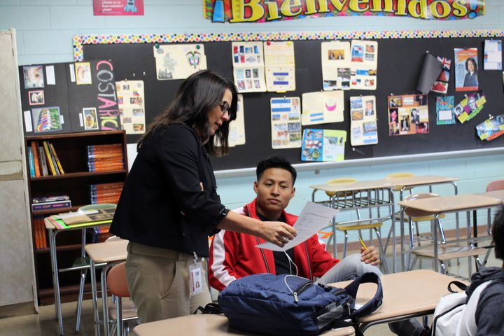 Dalimar Rastello, director of Patchogue-Medford school district's language programs, checks in on an immigrant student at the