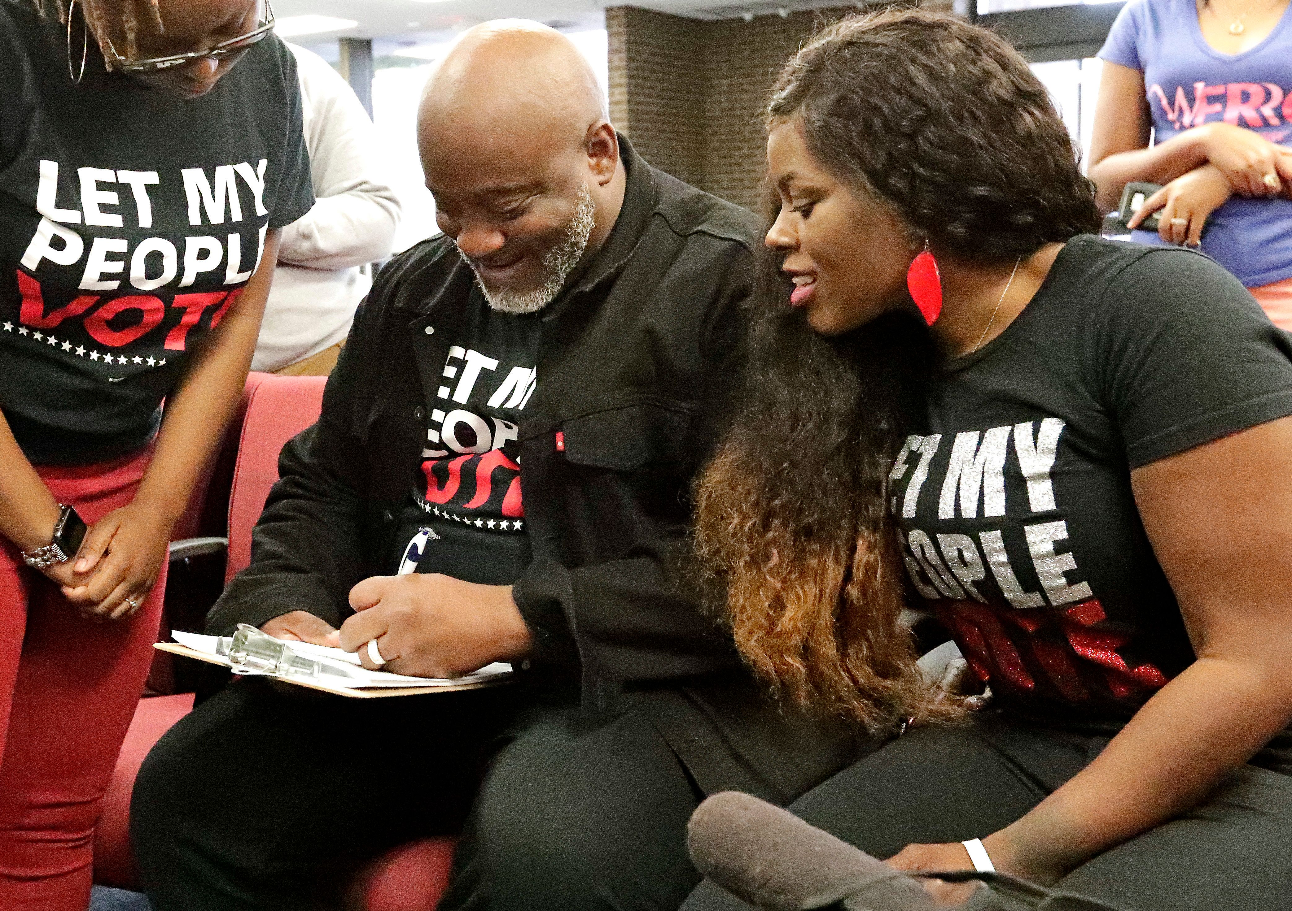 Former felon Desmond Meade and president of the Florida Rights Restoration Coalition, left, fills out a voter registration form as his wife Sheena looks on at the Supervisor of Elections office Tuesday, Jan. 8, 2019, in Orlando, Fla. Former felons in Florida began registering for elections on Tuesday, when an amendment that restores their voting rights went into effect. (AP Photo/John Raoux)