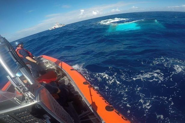 New photos show the moment US Coastguard rescuers approached the sunken catamaran off the coast of