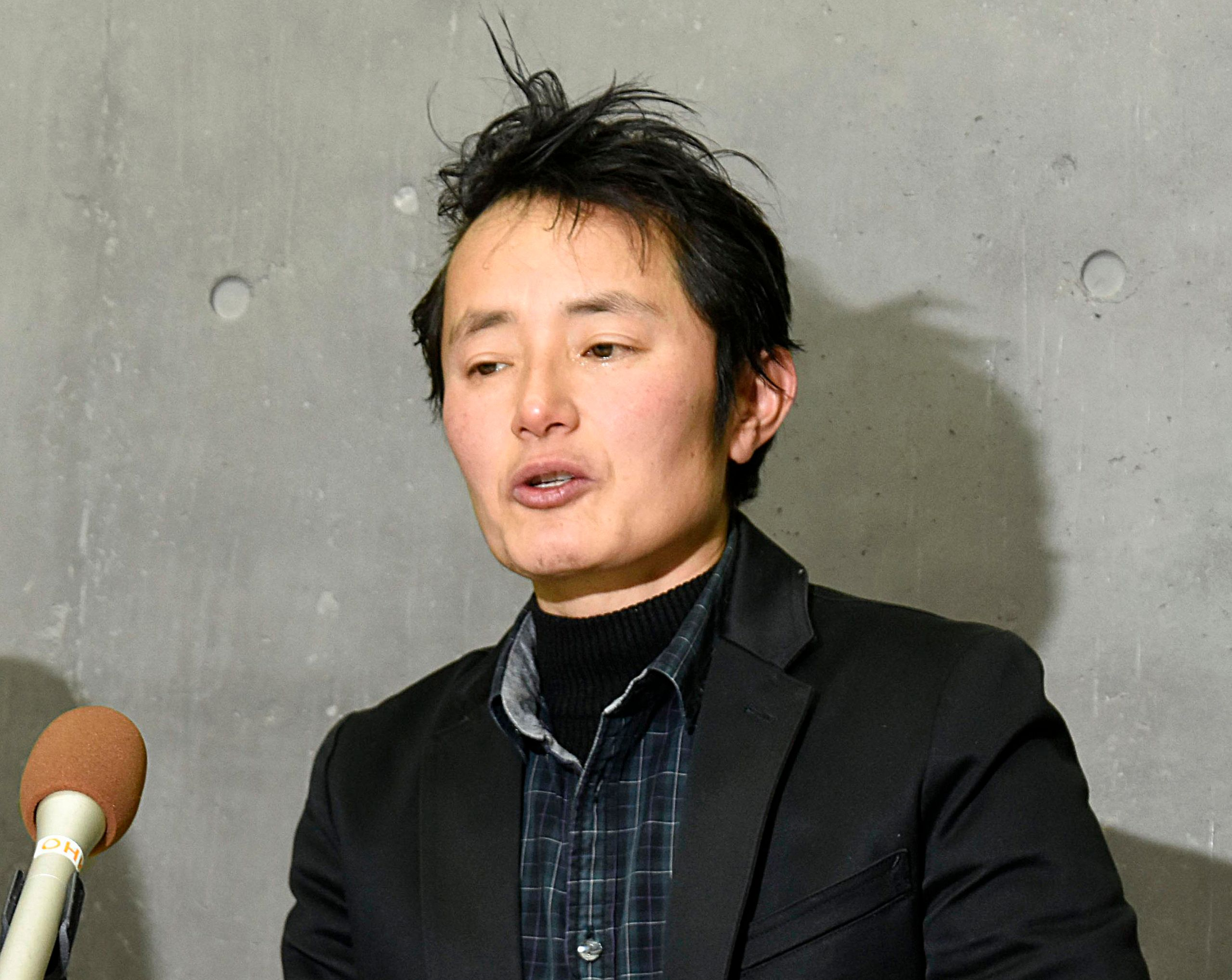 In this Thursday, Jan. 24, 2019, photo, Takakito Usui, a transgender man, cries while speaking during a press conference after Japan's Supreme Court handed down in Okayama, western Japan. Japan's top court has upheld a law requiring sterilization for transgender people to get their gender changed on official documents but acknowledged the law is increasingly becoming out of step with the international standard. (Kyodo News via AP)