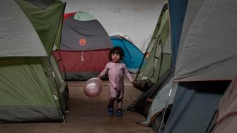 A girl holds a balloon as she walks among tents inside an empty warehouse used as a shelter set up for migrants in downtown Tijuana, Mexico, Wednesday, Jan. 2, 2019. Discouraged by the long wait to apply for asylum through official ports of entry, many migrants from recent caravans are choosing to cross the U.S. border wall and hand themselves in to border patrol agents. (AP Photo/Daniel Ochoa de Olza)