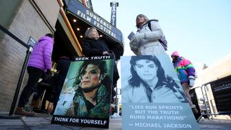 "Brenda Jenkyns, left, and Catherine Van Tighem who drove from Calgary, Canada stand with signs outside of the premiere of the ""Leaving Neverland"" Michael Jackson documentary film at the Egyptian Theatre on Main Street during the 2019 Sundance Film Festival, Friday, Jan. 25, 2019, in Park City, Utah. (Photo by Danny Moloshok/Invision/AP)"
