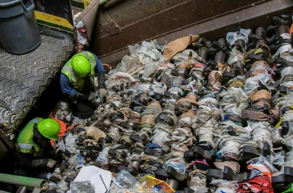 Workers at a Waste Management Inc. recycling facility try to detangle dozens of plastic bags stuck in...
