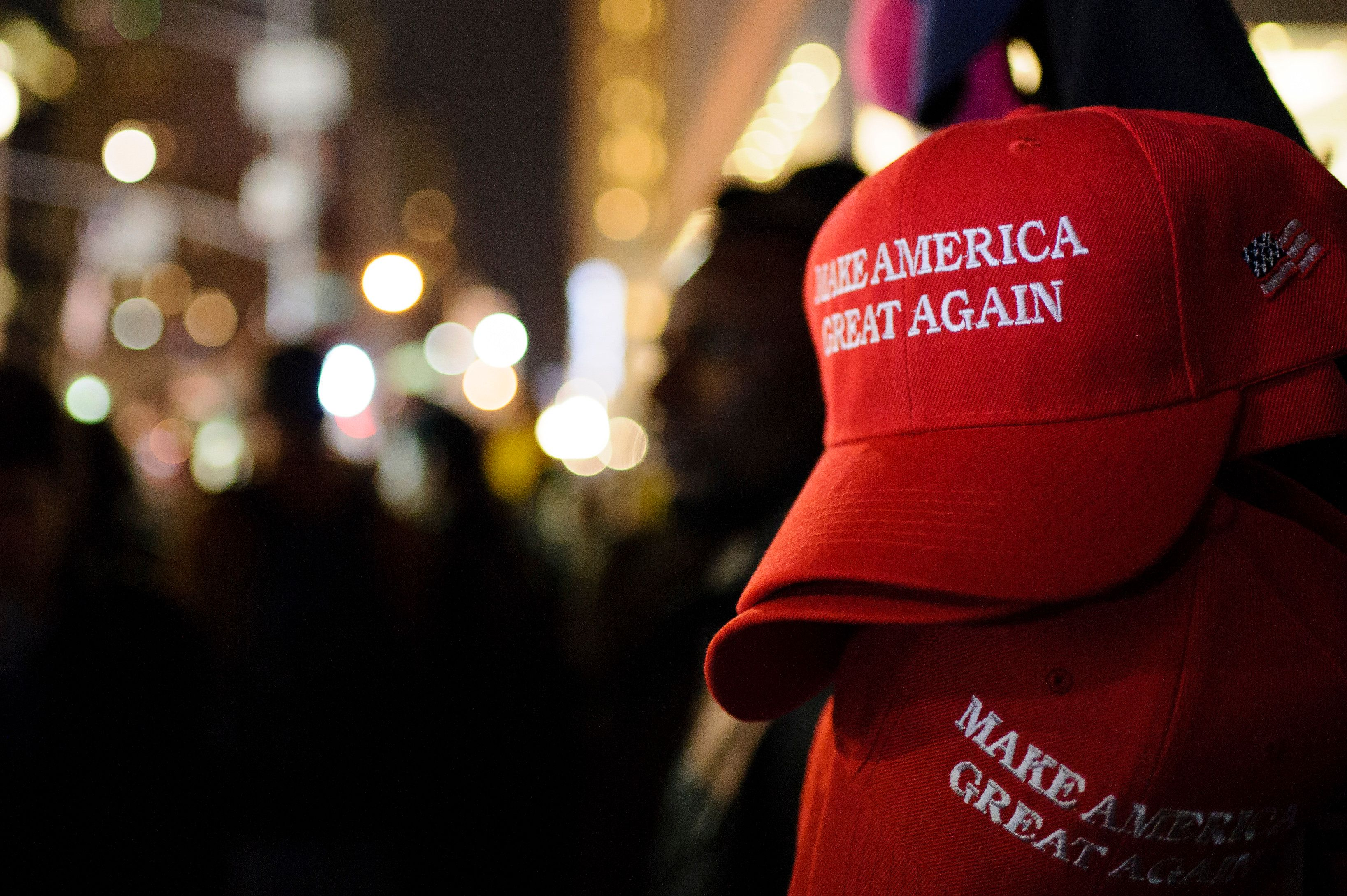 MANHATTAN, NEW YORK CITY, NEW YORK, UNITED STATES - 2016/11/09: 'Make America Great Again' red baseball caps, signature headwear of the Donald Trump campaign and its supporters, stand on sale on 6th Avenue in Midtown Manhattan in the second hour after Election Day as election results point to a shock Trump win. (Photo by David Cliff/SOPA Images/LightRocket via Getty Images)